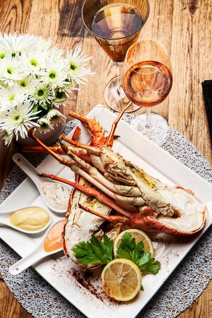Fabulous lobster dish on wooden table with wine and all the finesse of a luxury restaurant. Foto de archivo - 127926780