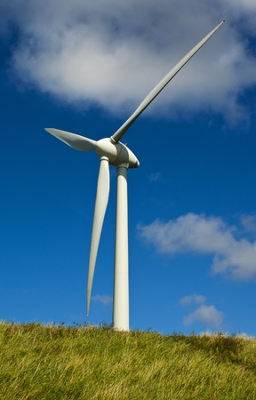 White windmill on a green grass and blue sky background Stock Photo