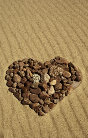 Heart made of stones in the sand