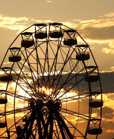Ferris wheel silhouette during sunset
