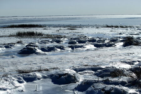Ice and snow during winter along the shoreline with blue skies