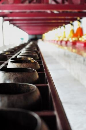 limosna: Filas de las limosnas del monje budista s cuencos en el Templo