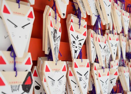 fox face: KYOTO, JAPAN - August 12, 2015: Wishing Fox Face at Fushimi Inari Taisha, the Shinto shrine famous for its thousands of vermilion Torii gates, which straddle a network of trails in Kyoto, Japan.