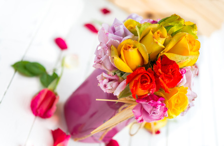 Colorful roses put in the purple vase or flowerpot