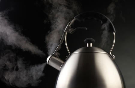 Tea kettle over dark background photo