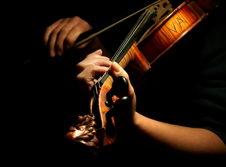 fiddles: Musician playing violin isolated on black Stock Photo