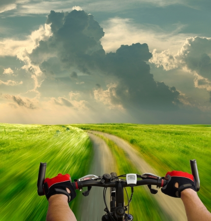 outdoor pursuit: Man with bicycle riding country road Stock Photo