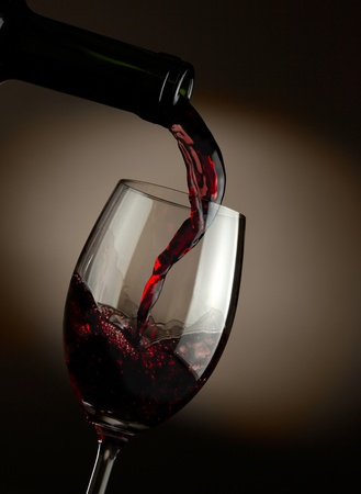 dark glasses: Red wine pouring in glass over dark background Stock Photo