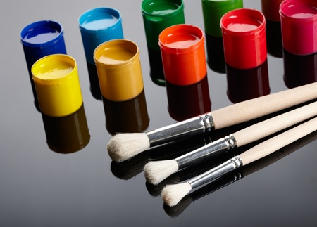 Paint buckets with paintbrushes over white background photo