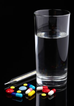 Pills, thermometer and glass of water over black background photo