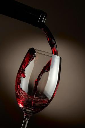 wine pouring: Il vino rosso versando in vetro su sfondo scuro