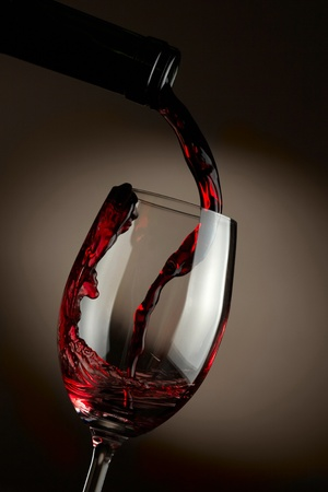 wineglass: Red wine pouring in glass over dark background Stock Photo