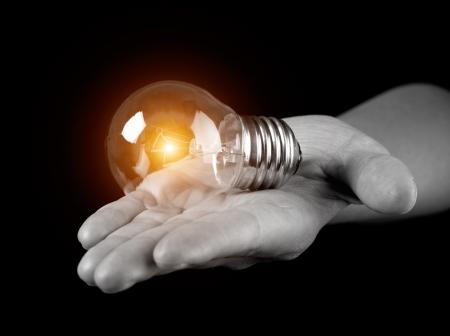 Ampoule à la main holding isolé sur fond noir Banque d'images
