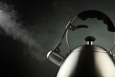 Tea kettle with boiling water photo