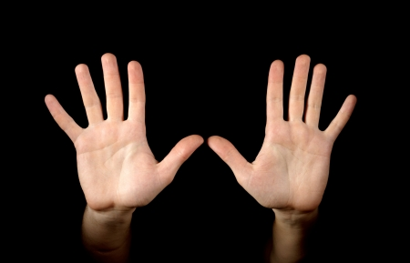 surrender: Hands isolated on black background