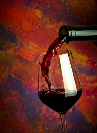 Red wine pouring in glass over grange background photo