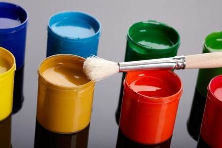 Paint buckets with paintbrush over dark background photo