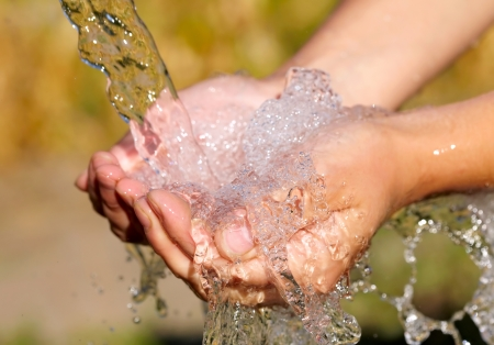 Womans hands with water splash Stock Photo
