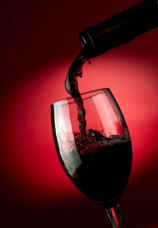 Red wine pouring in glass over dark background photo