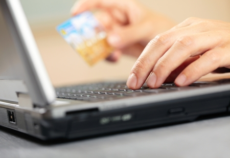 Hands holding credit card and laptop. Shallow DOF  photo
