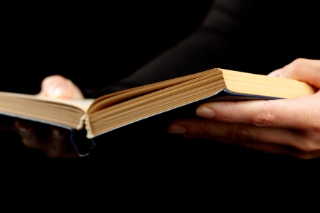 bookish: Open book in hands on black background
