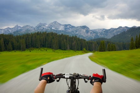 Man with bicycle riding mountain road photo