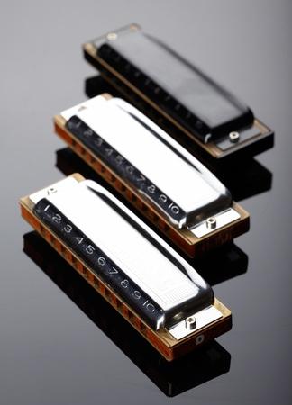 harmonica: Tree harmonicas on dark background