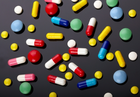 antibiotic pills: Colorful pills over dark background