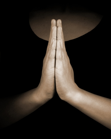 confession: Praying hands on black background