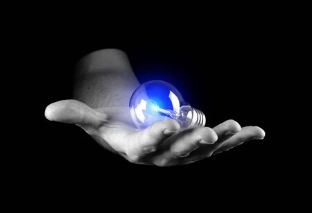 Hand holding light bulb isolated on black Stock Photo - 17607868