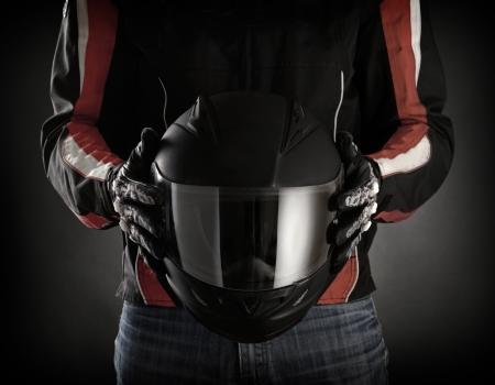 casco de moto: Motorista con el casco en la mano. Fondo oscuro