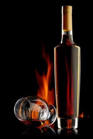 drunks: Bottle and glass of alcohol over dark background with flame