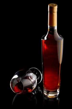 drunks: Bottle and glass of cognac over black background