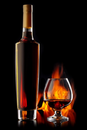 drunks: Bottle and glass of cognac over dark background with flame Stock Photo
