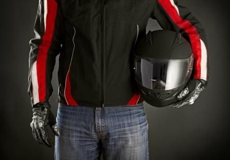 彼の手でヘルメットをバイクに乗る。暗い背景