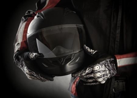 그의 손에 헬멧과 모터 사이클. 어두운 배경