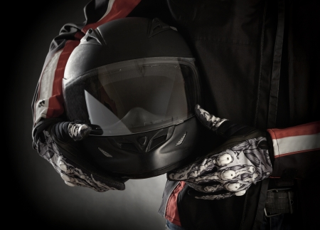 helmet moto: Motorista con el casco en sus manos. Fondo oscuro Foto de archivo