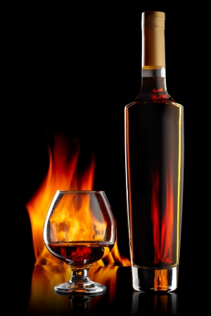 drunks: Bottle and glass with cognac over dark background with flame