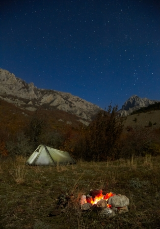 Campfire and tent in the mountains. Night, moonlight and stars photo