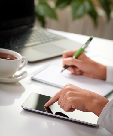 secretary desk: Woman hands with tablet PC and notepad at office