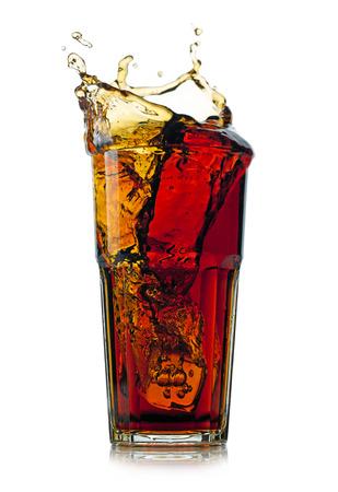 bebidas frias: Cola que salpica en el vidrio. Aislado en el fondo blanco