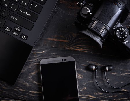 smartphones: Laptop, smart phone, photo camera and headset on wooden background
