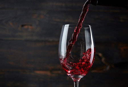 Pouring red wine into the glass against dark wooden background Stockfoto