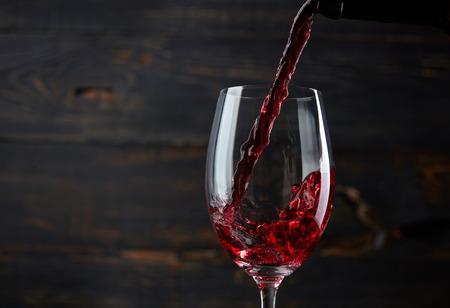 bebiendo vino: Verter el vino tinto en el vaso contra el fondo de madera oscura