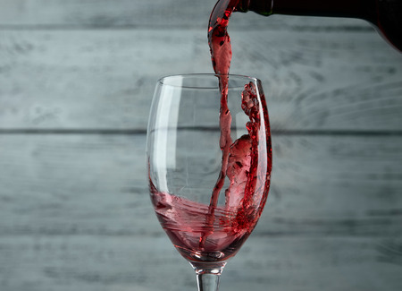 alcohols: Pouring red wine into the glass against grey wooden background
