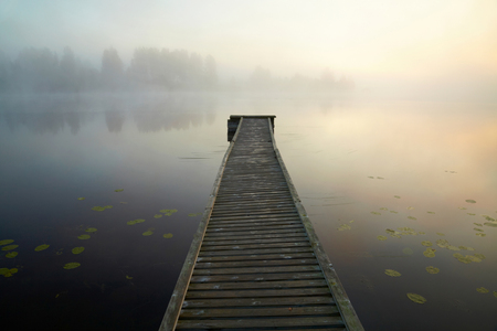 Wooden boat dock on the mysty lake. Finland