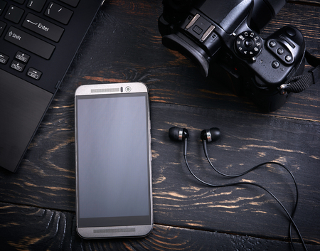 headphones: Laptop, smart phone, photo camera and headset on wooden background