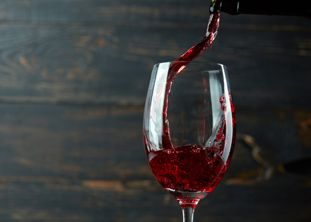 wine bar: Pouring red wine into the glass against dark wooden background Stock Photo