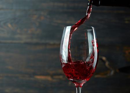 vino: Verter el vino tinto en el vaso contra el fondo de madera oscura