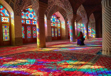 iran: SHIRAZ, IRAN - March 01, 2016: Young Muslim woman praying in Nasir Al-Mulk Mosque (Pink Mosque), Iran, Shiraz Editorial